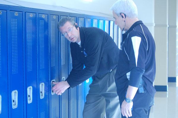 Security guards Ruge and Cima attempt to open a student's locker in a routine procedure