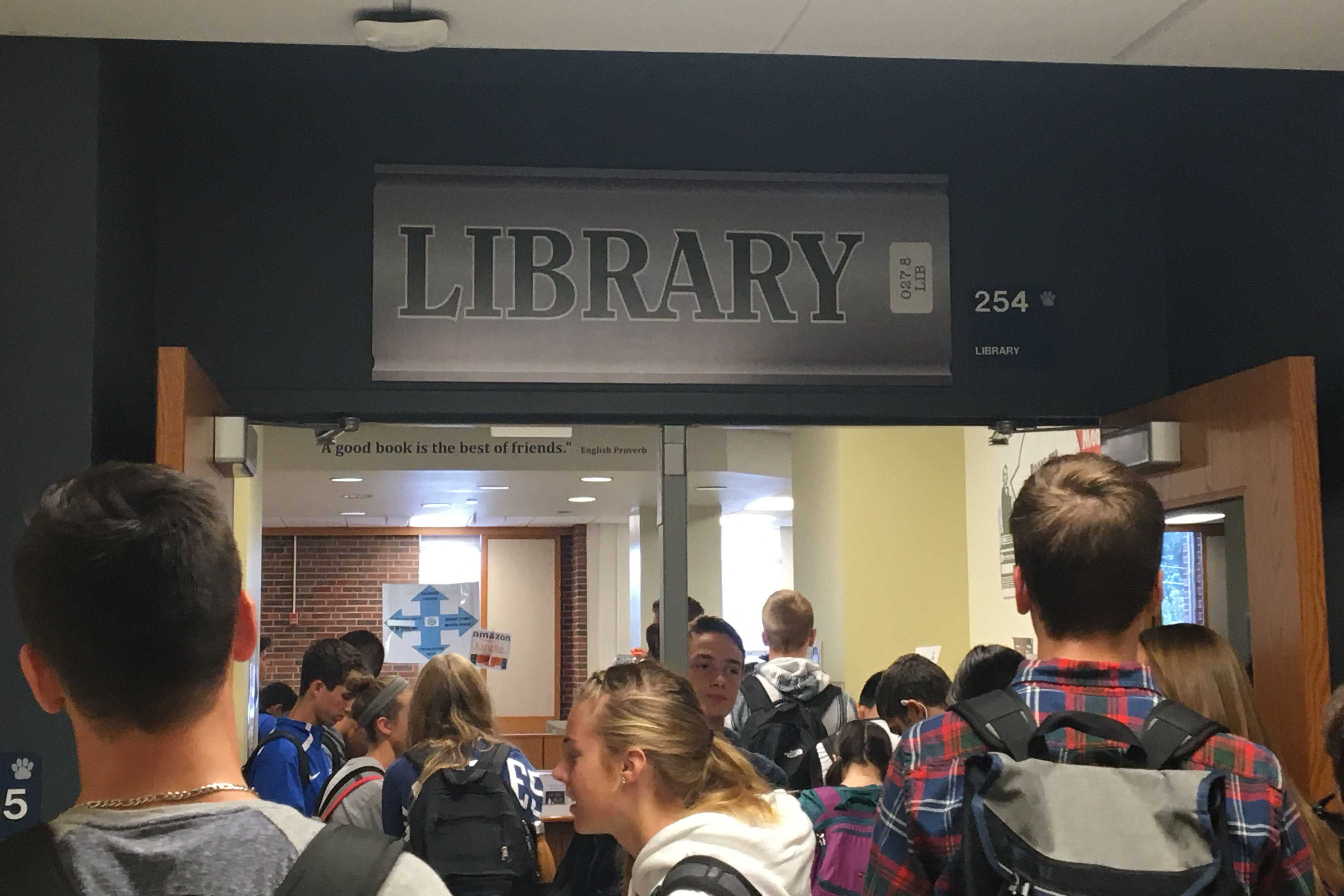 Students gather by library door waiting for it to open