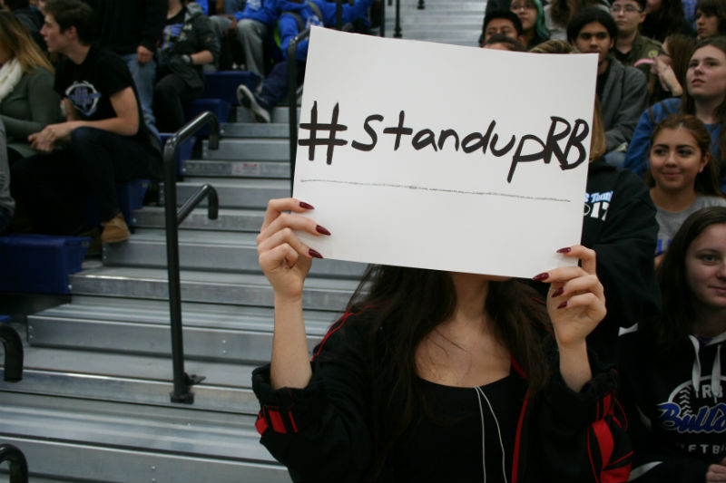 A+student+holds+up+a+%23StandUpRB+sign+in+solidarity+with+the+recent+protests+at+the+Pride+and+Positivity+Assembly.
