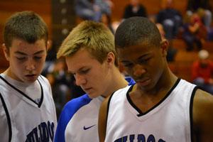 Sophomore boys huddle around their coach