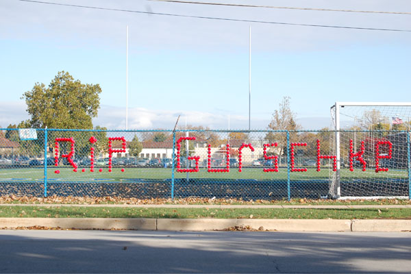 A memorial to Patrick Gurschke, spelled out in red plastic cups, graces the fence that runs along side the football field.