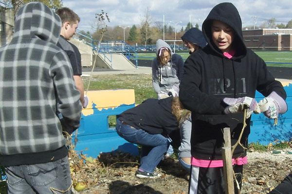 SEE Teamer Mac Catrambone and others stood in the Autumn chill to clear garden beds for a Fall garlic planting in the new End Zone Garden.