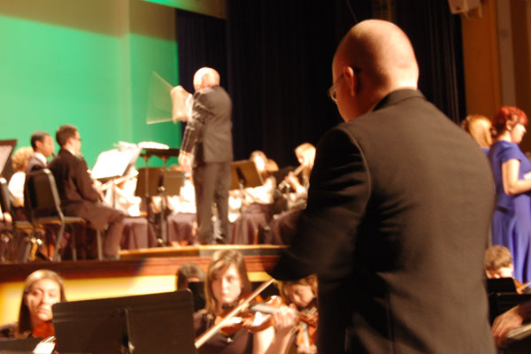 Fine Arts teacher James Baum directs in the foreground while retired and now part-time Fine Arts teacher Kevin McOlgan directs on the main stage for the Winter Holiday Concert.