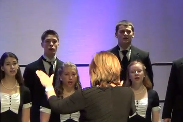 Fine Arts Department Chair and Madrigals sponsor Diane Marelli directs the singers at their performance downstate.  Marelli also acted as the piano accompanist during the entire IMEC event.