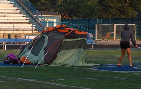 Lulu Keen takes down her tent after spending the night on the football field.