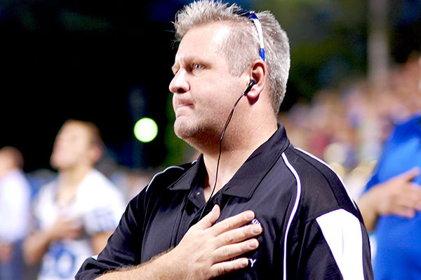 Security guard, Mr. John Gaines places hand over heart during the national anthem.