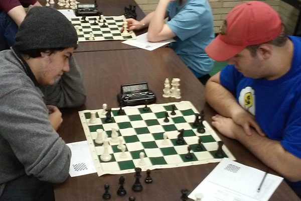 Two chess club players in the middle of an intense chess game.