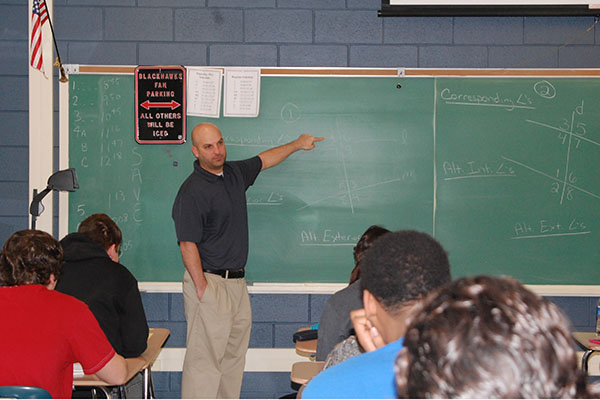 Bob Bensfield explains equations during an Algebra 2/Trig classes.  Bensfield co-teaches with Steve Yurek.  Currently, junior students choose between Algebra 2/Trig, a regular class, and Pre-Calculus, an honors class.