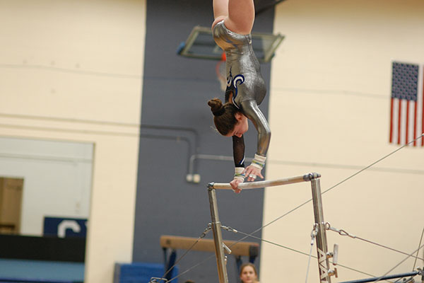Gymnast Lacey Smith in a hand stand on to top of the bar, a very advanced skill.
