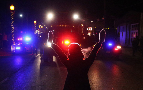 A protester raises her hands in the street as police use tear gas to try to take control of the scene near a Ferguson Police Department squad car after protesters lit it on fire.  RBHS was curiously silent through these events.