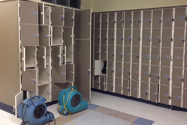 Two heavy duty fans work to dry out music lockers.  Lockers and instruments were damaged when a pipe burst, flooding the area.  The flood occurred the first weekend back from Winter Break.