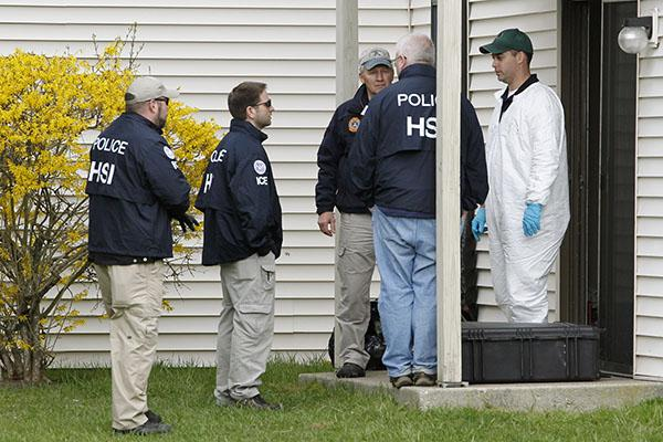 Federal crime scene investigators stand at the back entrance of an apartment on Monday, April 22, 2013, that belonged to two men who allegedly had ties to Dzhokhar Tsarnaev. (Matthew Healey/Boston Herald/MCT)