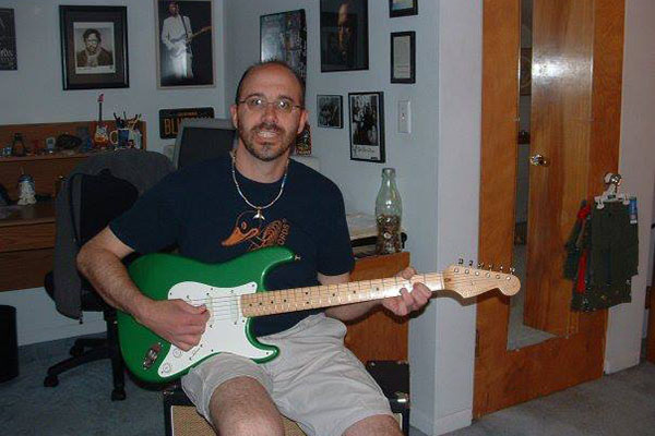 Science teacher Dave Monti poses with his green guitar.
