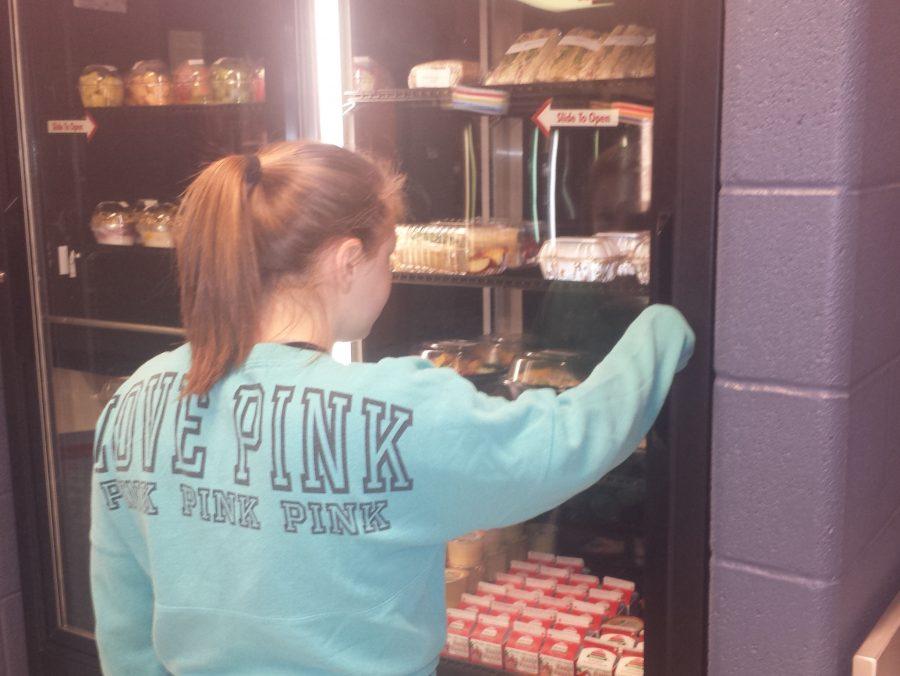 Student grabbing her lunch out of the fridge.