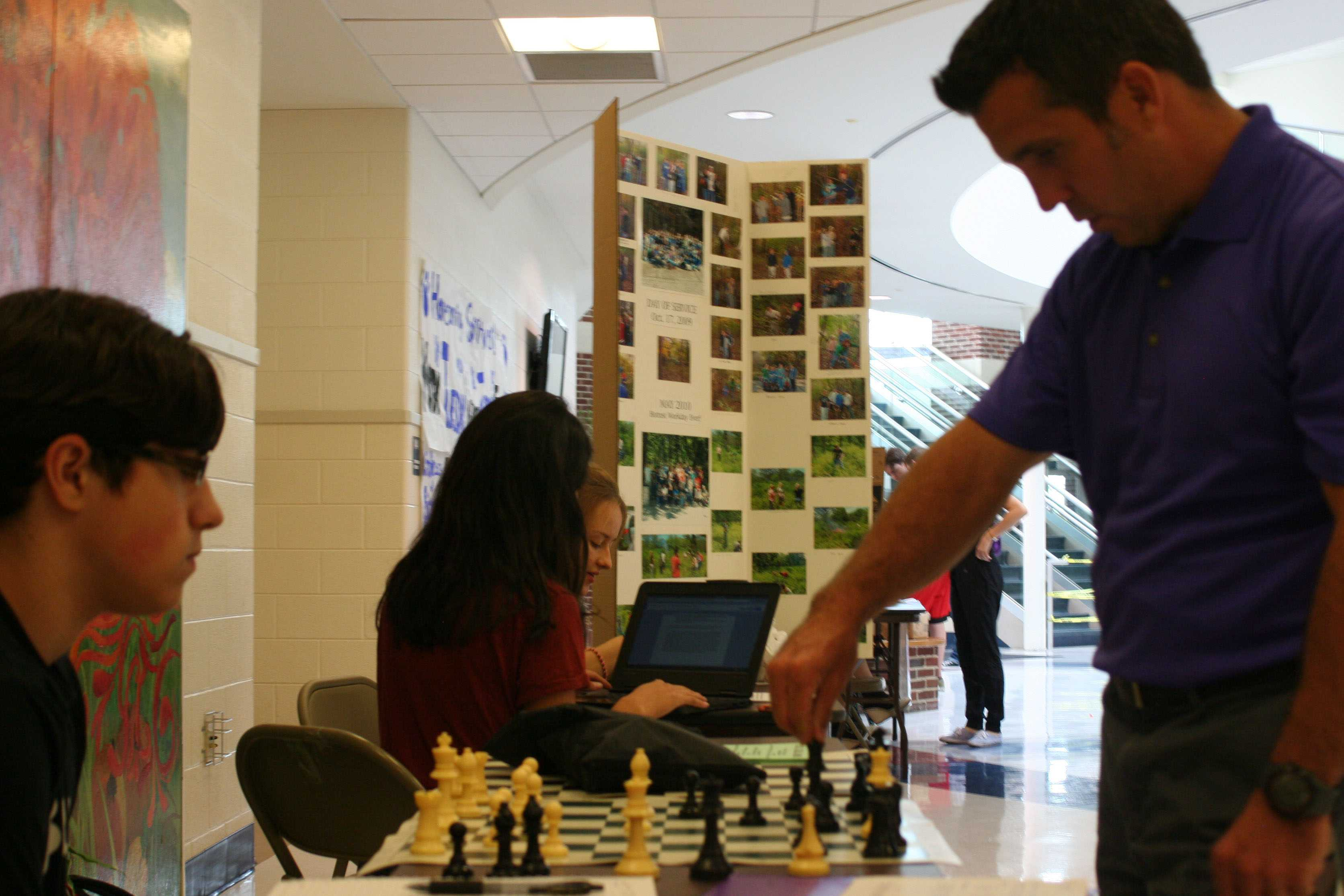 Dean Neil Dughetti and Jackson Hajer play chess at the Chess Club table.