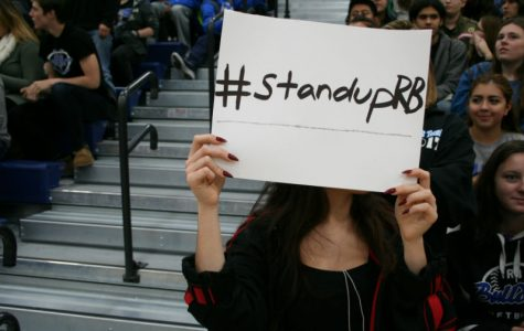 A student holds up a #StandUpRB sign in solidarity with the recent protests at the Pride and Positivity Assembly.