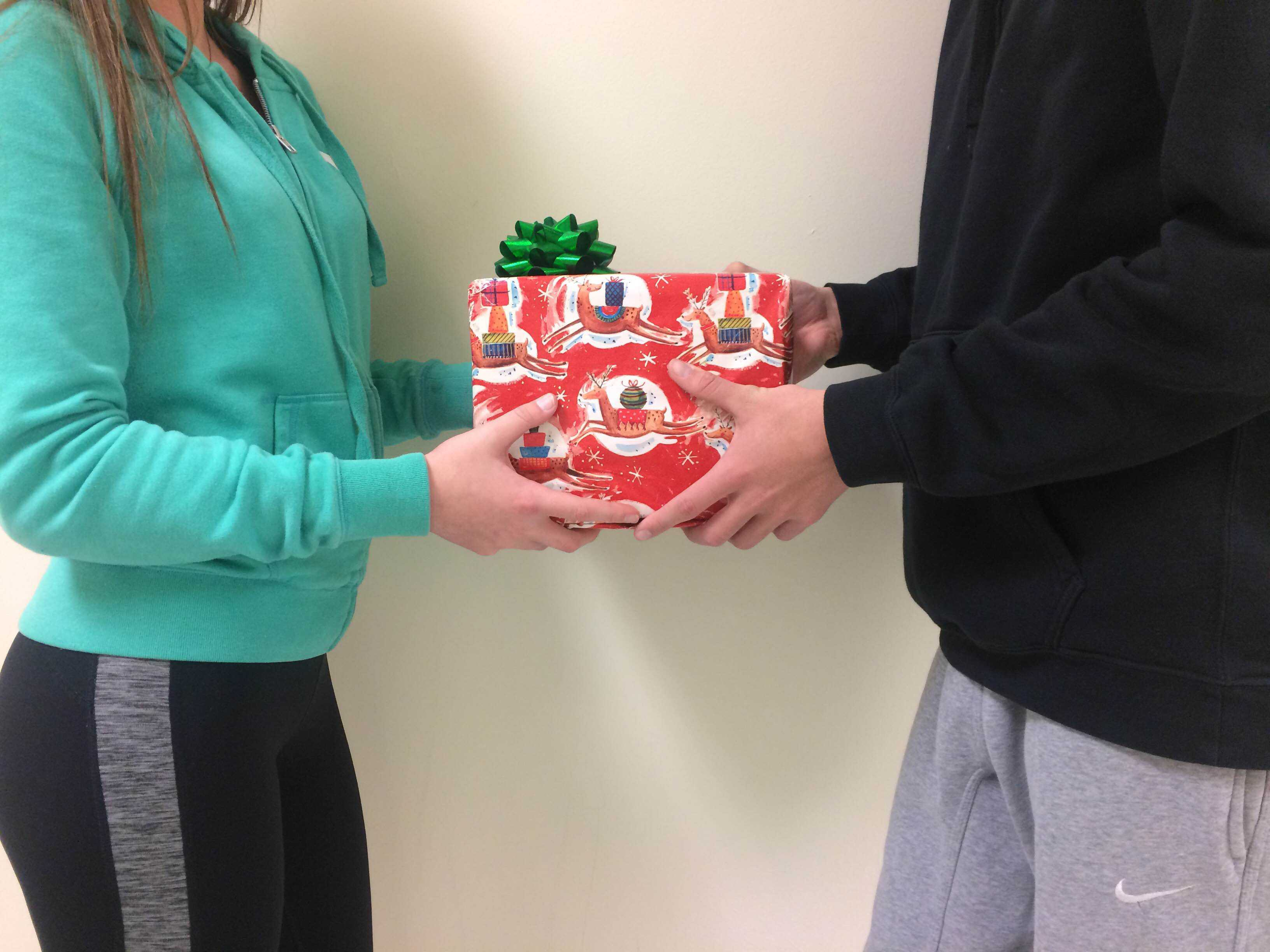 Two RBHS students exchanging gifts.