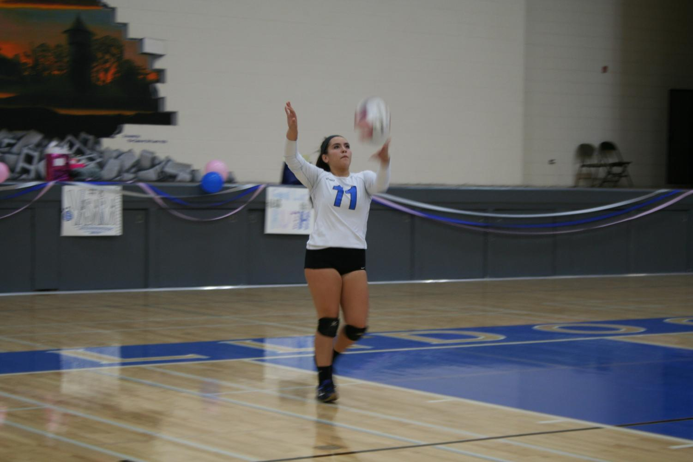 Senior, Maya Diaz serving in the Senior Night game.
