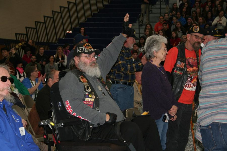 Veteran raises his hand when his branch is called during the Veterans Day assembly.