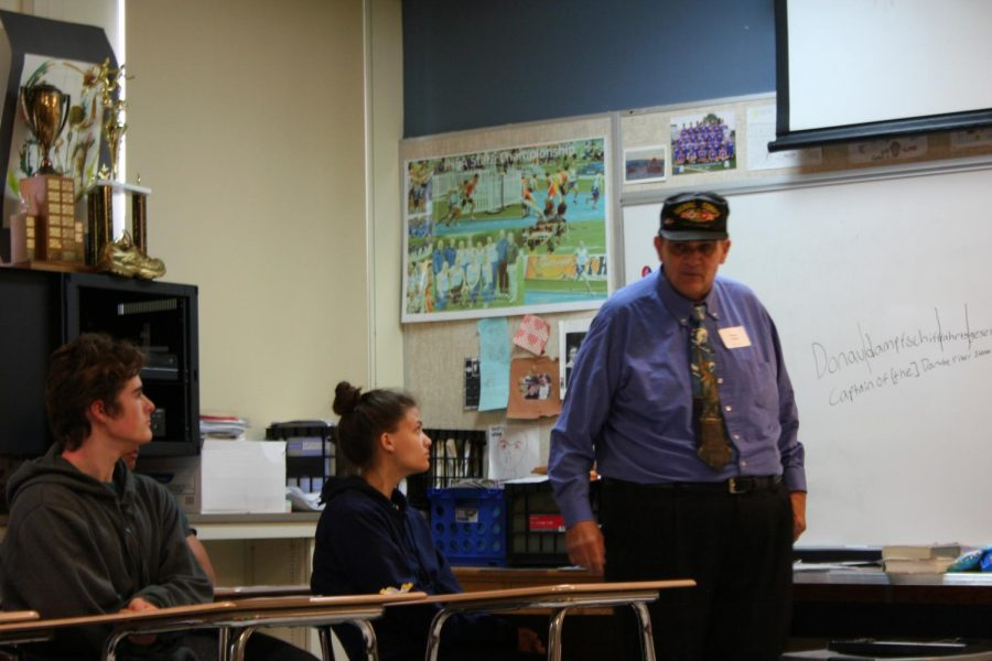 Students listen Veteran Bruce K Troyer on Veterans Day
