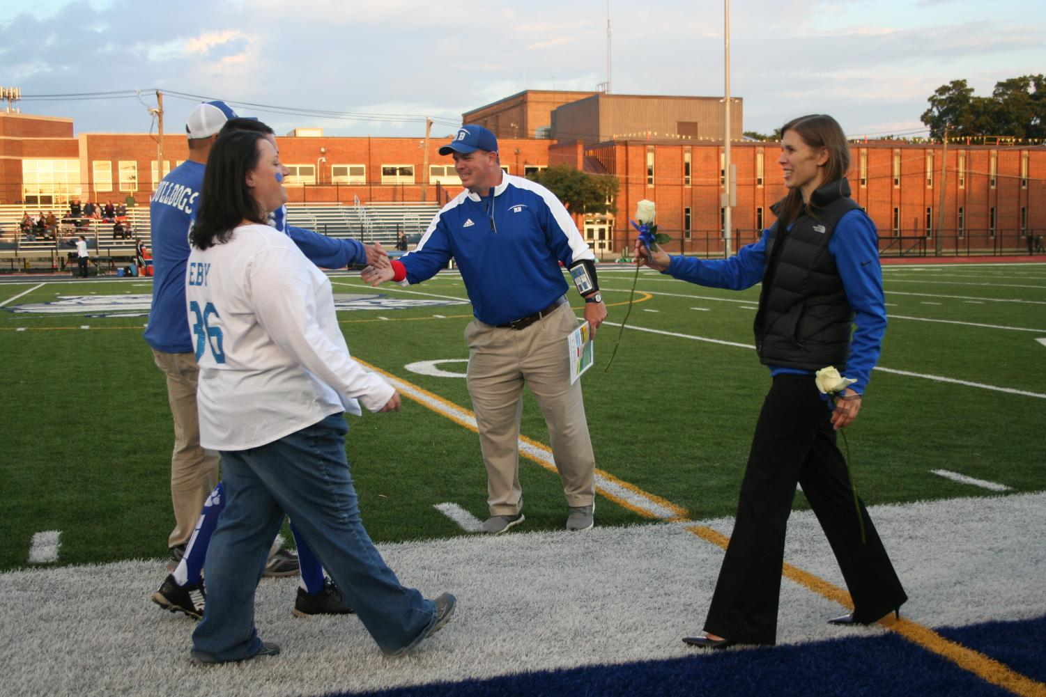 Curtin shakes hands with parents during football's Senior Night.