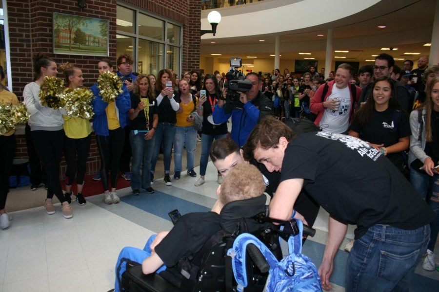 Ethan Tkalec was greeted by the student body as he entered the building today. Students McKenna Doyle and Jake Garvey share a moment with him during the clap-in.