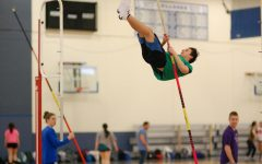 Archer Teran in the middle of a pole vault jump.