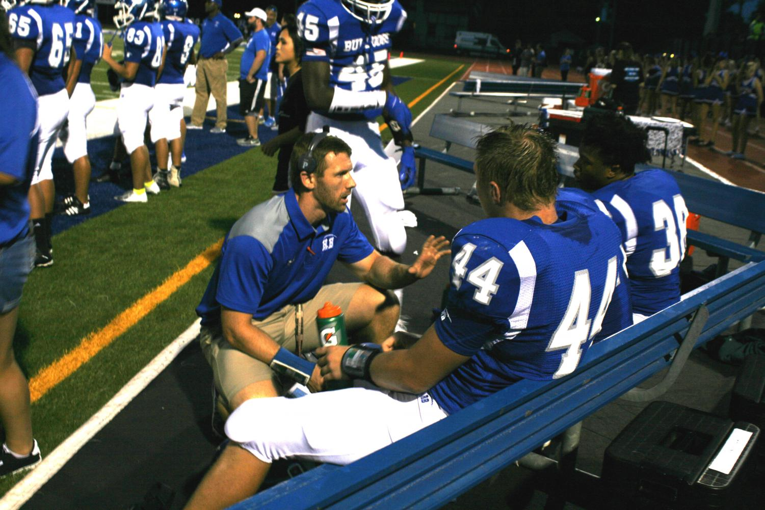 Coach William Duffy talking to players on sideline