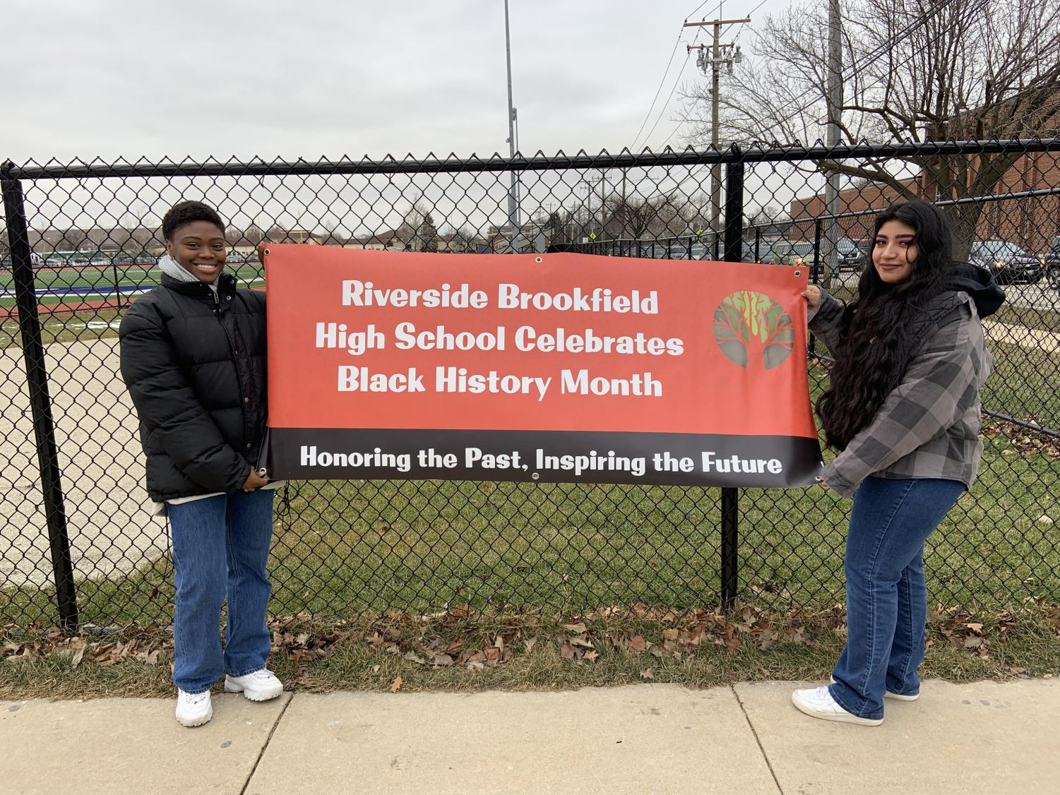 Shalah Russell and Miranda Bucio hanging up a sign for Black History Month.