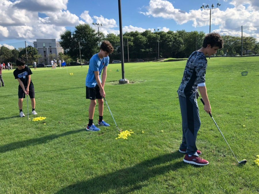 (From left to right) Andrew Agne, Evan Braniff,  and Trevor DeButch line up to putt in a JV practice.