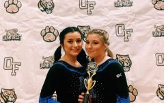Cerny (on the right) posing with a teammate at a competition in Oak Forest while holding a trophy.
