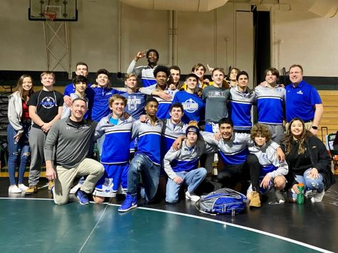 RB wrestling team posing after winning to advance to State.