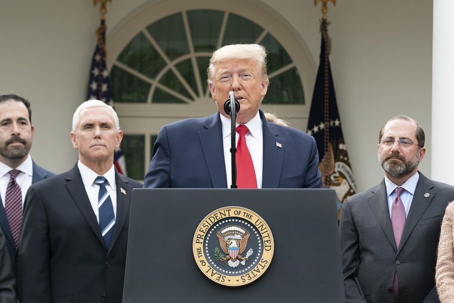 President+Trump+standing+at+the+podium+discussing+matters+related+to+the+coronavirus+and+his+administration+standing+behind+him.+