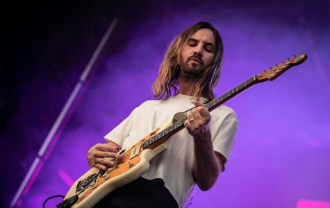 Tame Impala pictured performing, singing, and playing guitar.