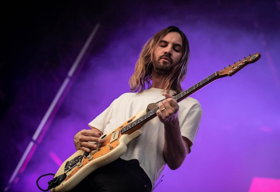 Tame+Impala+pictured+performing%2C+singing%2C+and+playing+guitar.+