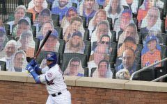 Yoenis Cespedes of the New York Mets standing practicing his swing in front of cardboard cutouts of fans.