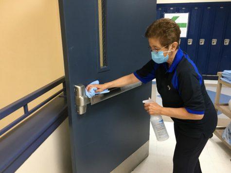 Maintenance worker Rosa Ramos sanitizing a door handle.