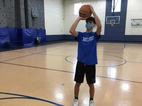 Sophomore Mohamed Douhabi attempts a three-point shot before practice. Photo taken by Clarion Staff.