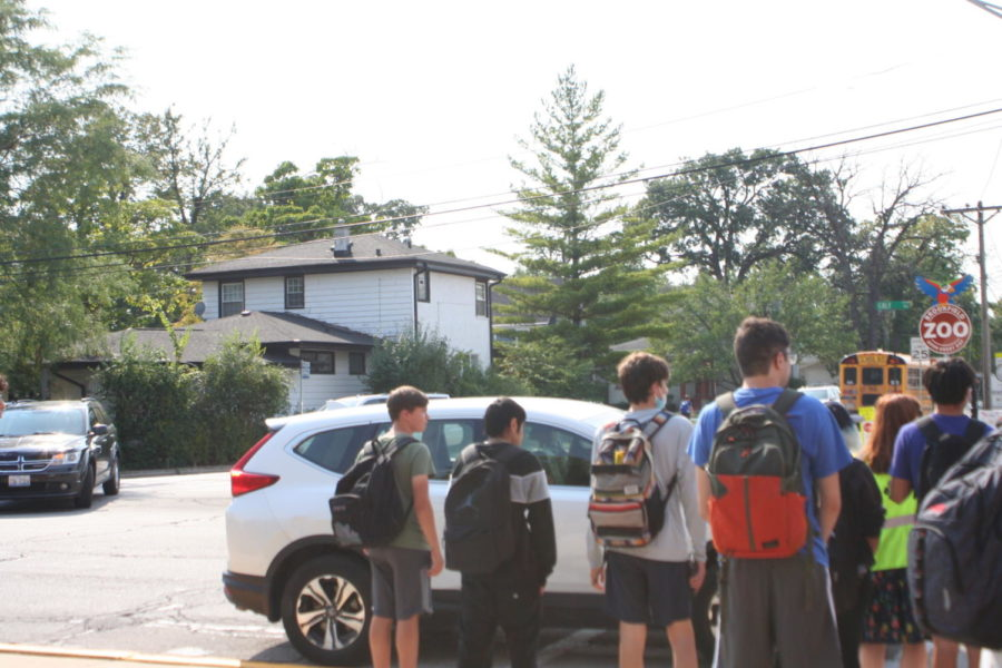 Students wait to cross the street in the after school traffic.
